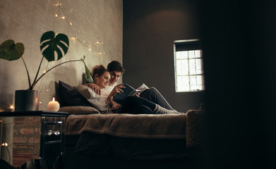 Couple reading book together on bed