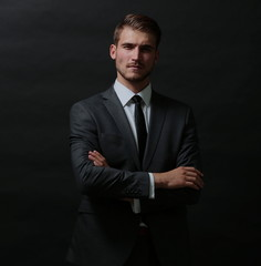 Handsome successful  business man isolated on black with arms cr