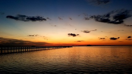 Foto op Canvas Donkergrijs Scattrered dark clouds with orange horizon after sunset over a fishing pier