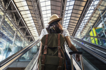 Young woman with backpack on travelator on international airport terminal.