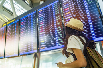 Young woman with backpack and carry on luggage in international airport, near flight information board.