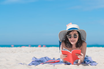 A picture of a girl relaxing on the beach reading a book.