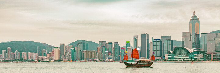Hong Kong skyline at sunset panoramic banner background with junk boat sailing in sunlight.
