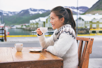 Iceland travel holiday happy Asian girl drinking coffee outside at restaurant wearing icelandic traditional wool sweater. Summer tourism holidays. Chinese multiracial woman tourist on vacation.