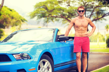 Young man new car owner driving convertible sports car on summer vacation. Beach lifestyle looking guy on spring break travel holiday. Handsome sexy topless male driver with abs feeling confident.
