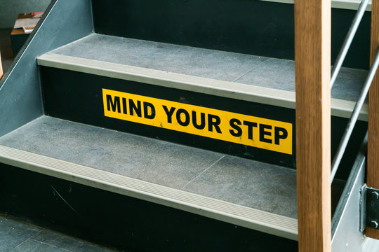 Staircase with mind your step warning sign