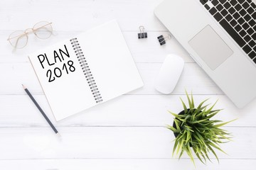 Minimal work space - Creative flat lay photo of workspace desk with Plan 2018 New Year list notebook and laptop on wooden background. Top view flat lay photography. 2018 happy new year concept.