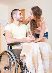 Loving boy in wheelchair with his girlfriend indoor