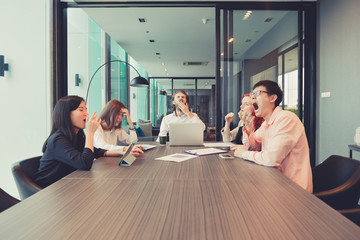 Group of business people yawning in a meeting room, sharing their ideas, Multi ethnic