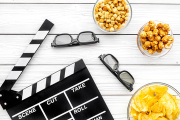 Crisp, popcorn, rusks for watching film. Clapperboard and glasses on white wooden background top view