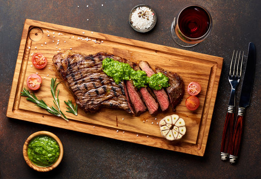 Grilled Black Angus Steak and a glass of red wine with chimichurri sauce on meat cutting board.