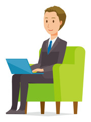 A young businessman is sitting on the sofa and operating a laptop computer