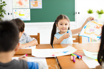 happy little girl drawing in the classroom