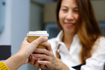 Young asia woman barista serving a diaposable coffee cup with smiling face at cafe counter background, small business owner, food and drink industry concept