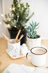 Mug of hot winter drink on table with home office details