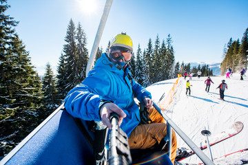 Skier wearing skis, helmet and mask sitting in ski lift cabin taking a selfie with a camera on monopod. Blue sky, sun, winter forest, ski slope with skiers on the blurred background lifestyle concept