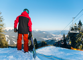 Full length rear view shot of a snowboarder standing in the mountains looking around enjoying beautiful winter day at ski resort copyspace sportsman sport seasonal recreation concept Bukovel