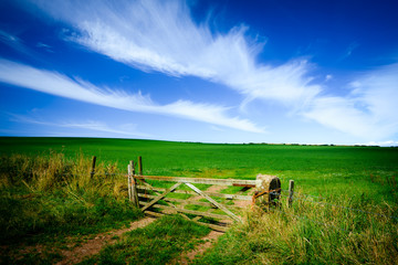 Below a blue polarised sky, an old wooden gate at the entrance to green pastures in the English countryside. Saint Bees Head Heritage Coast, England.
