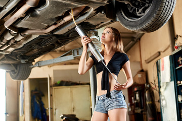 A young woman uses oil drainer for a lifted car