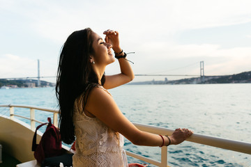 Young girl traveler relaxes while cruising on a yacht, looking at sunset and ocean, bridge in background