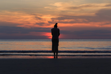 Woman sitting alone on the beach Silhouette style