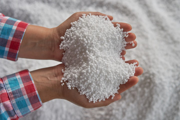 Nitrogen fertilizers or urea fertilizer in farmer hand. blur.white fertilizer background.
