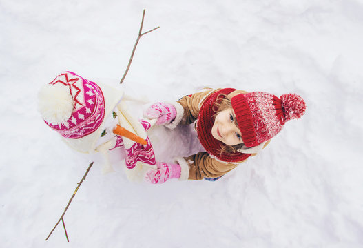 A child in the winter in the snow. To make a snowman. Selective focus.
