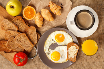 Plate with fried eggs, glass of orange juice, cup of black coffee, croissants, bread on wooden cutting board, fresh tomato, apple