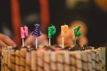 Close up of colorful Birthday cake candles with friends