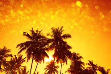 Palm trees silhouettes at sunset with party gold glitter lights bokeh overlay effect