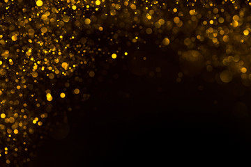 Shiny gold glitter flowing dust border frame on dark background
