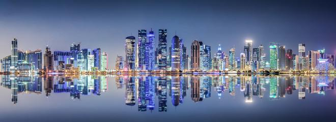 Die beleuchtete Skyline von Doha, Katar, bei Nacht Fototapete