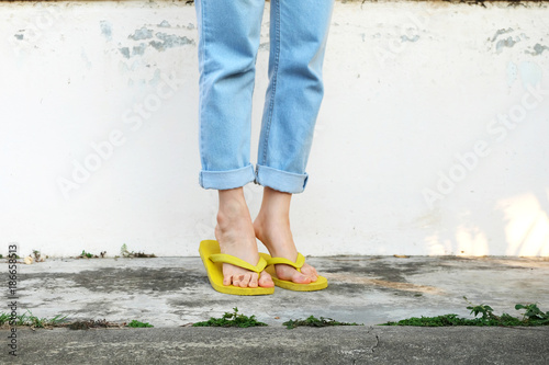 0102b1973632 Yellow Sandals. Woman Wearing Flip Flops and Blue Jeans Standing on Old  Cement Floor Background Great for Any Use.