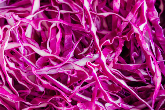 Close up sliced or shredded fresh purple or red cabbage in top view flat lay to present surface and texture of cabbage can apply for background or wallpaper. Vegetable pattern concept in macro style.