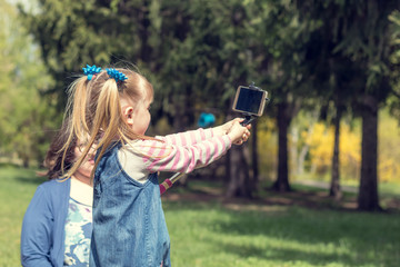 Cute little blonde girl with two ponytails taking selfie in the city park on a spring sunny day