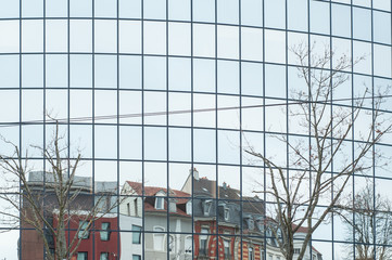 reflets d'immeubles anciens dans les vitres d'un immeuble vitré