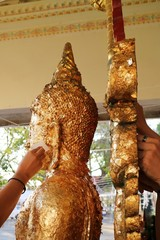 The hands put some gold leaf onto the Buddha image. Religion concept.
