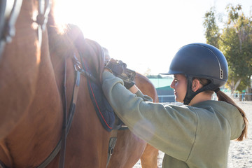 Cheerful teen girl in helmet putting saddle on back of horse.