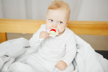 Baby takes rattle in mouth with serious face