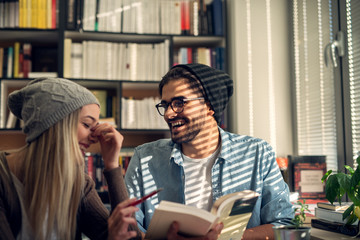 Close up of happy attractive beautiful hardworking stylish hipster young couple laughing while reading a book together in the library or classroom near the sunny window.