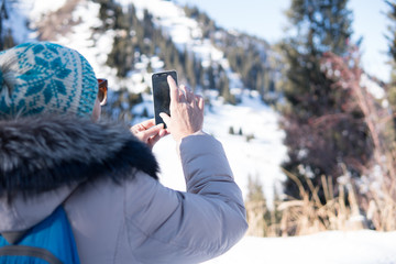Woman 50 years old taking photo in the mountains in winter, Almaty, Kazakhstan