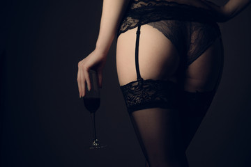 beautiful woman in stockings with glass red wine