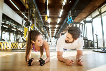 Close up front view of adorable smiling attractive girl doing plank while standing with her personal trainer in the sunny gym while looking each other.