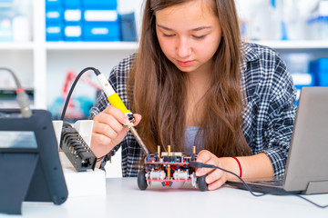 Schoolgirl in the school robotics laboratory with a robot model