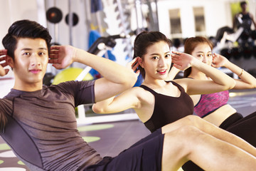 young asian people exercising in gym, focus on the girl in the middle