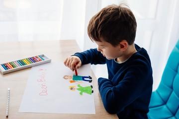 8 letni chłopiec maluje kredkami obrazek lurkę dla swojej babci na Dzień Babci