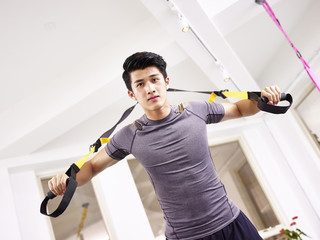 young asian adult working out in gym