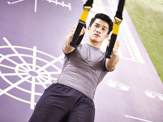 young asian adult working out in gym using straps