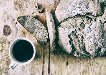 Loaf of homemade freshly baked bread and cup of coffee on the table