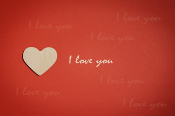 Love you concept. Wooden heart on red background